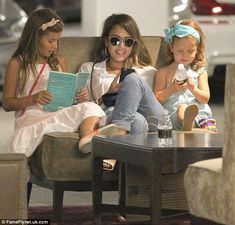 Heading home: The actress checked her phone while Honor read a book and Haven played with ...