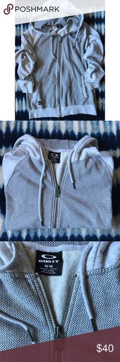 LIKE NEW • OAKLEY ZIP-UP BARELY WORN • OAKLEY ZIP-UP + HOOD • LABELED UNDER WMNS BUT IT IS A MENS SIZE MEDIUM • I LOVE BAGGIER FITS & THIS IS DEF A UNISEX HOODIE • TWO FRONT POCKETS + INSIDE MEDIA POUCH • LIGHT GRAY + SMALL BLACK CHEVRON PATTERN • LONG & COZY  📚☕️ OFFERS ALWAYS WELCOME Oakley Tops Sweatshirts & Hoodies