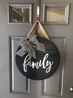 "18"" wood round door hanger - approx 1"" thick. The burlap hanger is about 6"" long. Wood round is stained black with metal family ***BOW may vary depending on ribbon availability. If an exact bow choice is preferred, please contact us before ordering Each door hanger is made to"