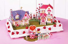 Celebrate Love  Help Cupid's arrow find romance by creating this simple vignette in your home.    VIGNETTE INSTRUCTIONS:  Materials:  Pink tablecloth  Serving tray  String of red hearts        Cover table with pink tablecloth.      Place serving tray on table. String hearts along the sides of the tray.      Place buildings inside the tray. Add accessories in front of the tray.      The cords should be pulled behind the buildings and over the lip of the tray behind the table.