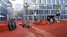 """Das erste öffentliche Wohnzimmer der Schweiz breitet sich im St. Galler Bleichi-Quartier unter freiem Himmel aus. Es ist mit rotem Gummigranulat überzogen und wird von kunstvollen Leuchtkörpern beleuchtet. Die """"Stadtlounge"""" der Künstlerin Pipilotti Rist und des Architekten Carlos Martinez lädt zum Entspannen und Staunen ein."""