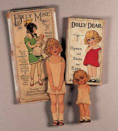 """German mechanical eye paper dolls. 7"""" Dolly Dear's eyes open and close by moving easel back up and down, box marked Socolu, No 392A. 11"""" Dolly Mine's eyes also open and close by moving easel back up and down, marked S&C, Series No 386. Both circa 1920s."""