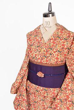 ベージュ地にこっくりとした赤のバリエーションを基調に織りだされた花と実のようなボタニカルデザイン美しいウール単着物です。