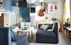 Séjour/salle à manger meublé de canapés modulaires, mur composé de différentes éléments de rangement, tables basses et tables de salle à manger sur tréteaux