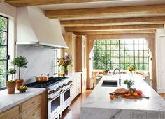 """In a 1920s Tudor house, Jeremy Corkern and Thomas Paul Bates were given a challenge: Design a kitchen that reflects the past as well as the present. New steel casement windows echo the period, but the island feels more contemporary with its waterfall edge. Quartersawn white oak was bleached, limed, and then waxed to make the cabinets. """"The liming wears off around the knobs, and that creates patina, so it looks both warm and modern,"""" says Corkern."""