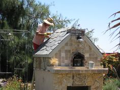 Our Pizza Oven is almost finished, just putting on the last of the slate on the roof! It is really a very pretty pizza oven, faced with travertine tile and Golden rock. Opening below is for wood storage.