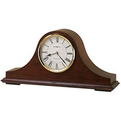 """The Howard Miller Christopher 635-101 Mantel Clock features a off-white dial and convex glass crystal, polished brass finished bezel, black Roman numerals and brass second hand. Quartz, battery operated movement will play Westminster chime melody on the hour and also count the hour. Finished in Windsor Cherry on select hardwoods and veneers. Chimes silence with the automatic nighttime chime shut-off feature. H. 8-1/2"""" W. 17-3/4"""" D. 4-3/4"""""""