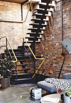 Exposed red brick walls are paired with polished concrete flooring in this industrial-style home. This black staircase features bright yellow handrails as a visual statement. Warehouse Living, Warehouse Home, Warehouse Design, Industrial Stairs, Industrial Living, Industrial Style, Vintage Industrial, Industrial Design, Beton Design