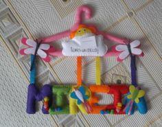 Percha con nombre forrada y decorada con diferentes motivos, ideal para decorar una zona infantil o como regalo.