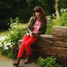 Pink graphic t-shirt, red jeans, boots, bomber jacket