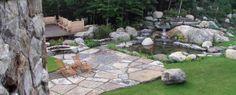 Petite cascade d'eau et son bassin. Un extérieur avec terrasse et aménagement de divers murets. Réalisation Maxhorti au Québec, dans les Laurentides. #Landscaping