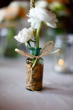 tiny bottle vases tied with twine - create labels to go around them or use lace and burlap