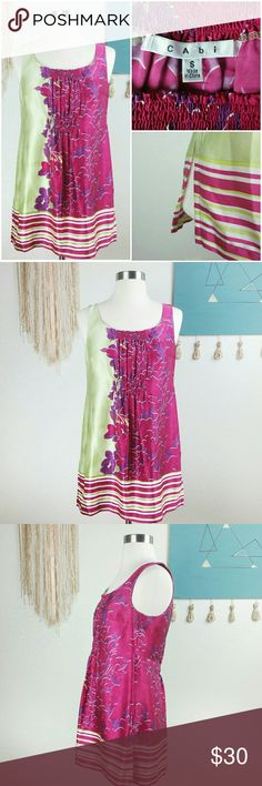 """CAbi Silk Floral Tunic Top Small Sleeveless crew neck tunic top featuring a fuchsia pink and purple floral against a lime green background set off by a complimentary striped hem. Ruched gathered neck line and panel under bust. Style #103  Bust 16"""" Length 28"""" 100% Silk  Thanks for checking out my closet and Don't forget to LIKE for a special offer! ! BUNDLE your likes and I'll send you a discount! CAbi Tops"""