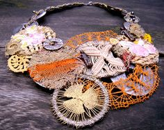 """Tota reciclados  (Marcela Muñiz & Valeria Hasse)  Necklace: Untitlesd  Old pieces of embroidery and knitted material, found textiles, acrylic paint, wool threads, wire, old straw bags, found metallic pieces  28 x 21 cm  Serie """"Textiles"""""""