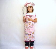 """Une jolie idée de cadeau pour une petite princesse des cupcakes ^^ Tablier et toque en coton imprimé de cupcakes dans les tons roses et mauves sur fond rose clair avec des pois écru. Une poche ventrale en coton rose clair est cousue sur le tablier. """"la..."""
