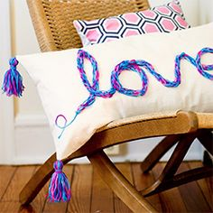 """Make this fun tasseled finger knit """"love"""" pillow. Great tassel directions, too!"""