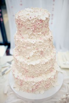 ~ gorgeous wedding cake...the pink coloring is so soft and subtle and the texturizing done by the flowers and edible pearls is just beautiful.