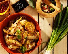Pittige chili knoflook kippevleugeltjes met Aziatische touch door toevoeging van gember en koriander.