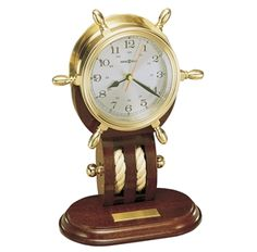 """613-467 Britannia Polished and lacquered solid brass ship's wheel clock rests on a mahogany base which features nautical rope and brass knob detailing. Spun silver tone Arabic numeral dial and 24-hour time track. Beveled glass crystal. A 1"""" x 2 1/2"""" brass self-adhesive, engravable plate with polished beveled edges is included. Quartz movement requires one AA sized battery (not included). Overall Dimensions: Height 12.5"""" (32 cm) Width 8.5"""" (22 cm) Depth 5"""" (13 cm)"""
