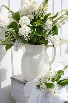 a bouquet of white lupines and lilacs in a white pitcher