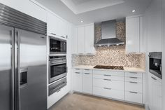 Without detracting from the crisp white and gray palette of this kitchen, a mosaic tile backsplash adds speckled texture behind the cooktop.