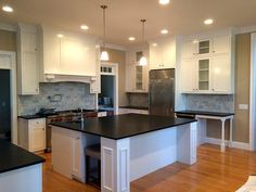 A white kitchen with a large island and desk unit. #custom #wood #kitchen #cabinet #remodel