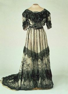 1900s Alexandra black lace on white evening dress  This white dress with spangled black lace bertha and over-dress is for the girl who has everything.
