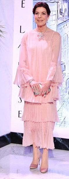 Princess Caroline of Hanover, opted for a softer look in a tiered powder pink dress. She teamed the flirty frock with a pair of rose pink velvet shoes, metallic silver clutch and an oversized starfish necklace, beaming as she arrived for the black tie event in Monaco.