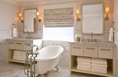 Claw foot slipper tub with easy access to faucet and for cleaning. Elegant and practical bathroom. Lovely Roman shade.
