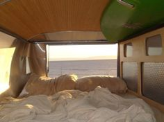 VW Bus on the Beach | Shallow ceiling and window taking up all of the space near the headboard
