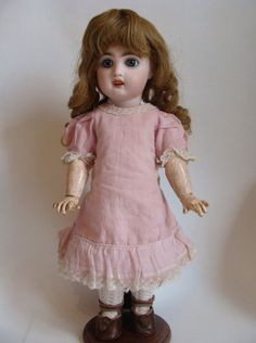 """Poupée Ancienne Jumeau t6 Poupée Ancienne Jumeau t6 This little doll around 1900 size 14inchs (t6) is very cute. The bisque head has a really nice expression with a red stamp behind the head """"TETE JUMEAU"""". The body is in good condition, with a blue stamp on the back """"Bébé Jumeau, diplôme d'honneur"""". She wears original clothes except handmade socks. She has a cotton pink dress, one underwear with embrodery, an apron with stripes, and original leather shoes."""