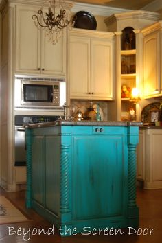 I love the idea of the white or cream cabinets and then an island in the middle with a pop of color.