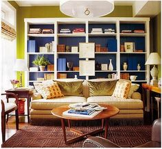 love the blue bookshelf backs contrasted with white and green.  comfy looking couch and pillows.