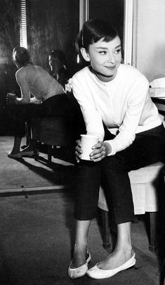 Audrey Hepburn.  Take a note girls, this is one of the hallmarks of being a lady: sitting with your legs together even when you're wearing pants!