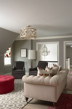 Chic living room design with pigeon gray walls paint color, light gray painted ceiling, charcoal gray velvet curvy accent chairs, ivory tufted chesterfield sofa, round red tufted storage ottoman, octagon drum pendant chandelier and ivory & gray fretwork rug.