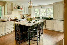 Kitchen with cream cabinets and black island -- Sawhorse Designs