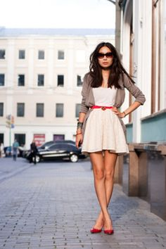 Long beige cardigan belted over white dress, red pumps