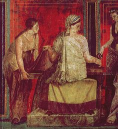 Demeter (or the officiant acting as Demeter) -- He^ Mystis --is seated, with her back toward us. She is assisted by two ladies, one of whom is pouring water on her hand (or an apparently laurel branch she is holding), while the other has provided a tray (presumably with sliced bread), which Demeter isuncovering. She consecrates the bread bya sprinkling (as it is usually done over animals to be sacrificed, or, more importantly, as the Sky does to make the seeds germinate), and she will…
