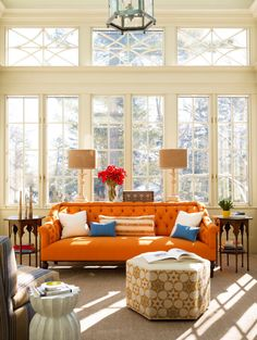 an art deco ottoman adds charm and interest. the orange sofa is a bright surprise!