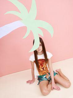 Katrina Tang Photography for Babesta boutique NY Safari SS 14 kids fashion. Girl sitting under a palm tree, beachwear, pink wall #katrinatang #tangkatrina