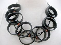 Black rubber rings, double strand, on a black rubber cord. Toggle closing.