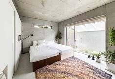 Simple blissful, minimal, industrial style room with conrete walls and roof, coloured rug and soft, white bedding. The House supplies a monotonous street with a passing view by Kenji Yanagawa Architect and Associates