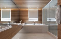 The bathrooms saw the least significant changes. In the one nearest to the master bedroom, the shower and tub are original. White oak paneling provides continuity between the newly renovated spaces. Grey Bathrooms, Master Bathroom, Bathroom Gadgets, White Oak Wood, Oak Panels, Pink Bedrooms, Residential Interior Design, Residential Architect, Architect House