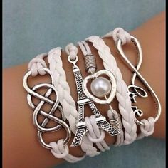 Eiffel Tower, love, infinity, and pearl bracelet. White leather adorned with an infinity symbol, pearls and the Eiffel Tower all make up this unusual bracelet. Jewelry Bracelets