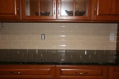grey glass subway tile backsplash with cherry cabinets and black