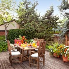 A bristlecone pine and a blue spruce screen this cedar dining deck. Containers filled with summer annuals—marigolds, petunias, impatiens, and vining mandevilla—soften the corner near the potting shed, bringing colorful blossoms close enough for guests to enjoy. | Photo: Mark Lohman.| thisoldhouse.com