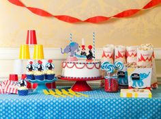 use red cups - cheap and yellow utensils are super cute. love those napkins too ... with the blue tablecloth :)  btw - free printables on this site