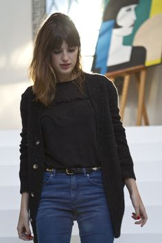 Jeanne Damas - black slouchy cardigan, high waisted jeans, and silver accent belt.