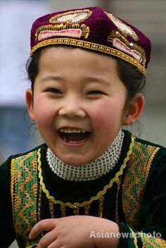 Yue Jiaxuan, a girl of the Hui ethnic group, smiles as she plays with other pupils at Lanzhou Qing Hua Primary School, in Lanzhou, capital of Northwest China's Gansu Province, March 15, 2008