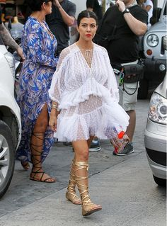 Kourtney Kardashian wears a white sheer lace dress with gold lace-up sandals